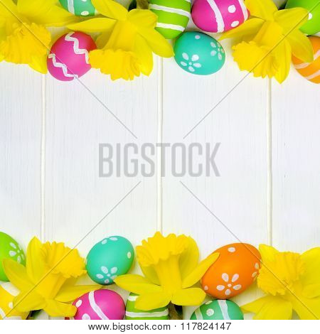 Easter eggs and daffodils double border over white wood