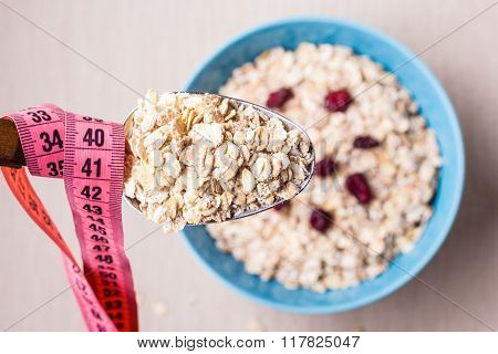 Oatmeal In Bowl And Measuring Tape Around Spoon