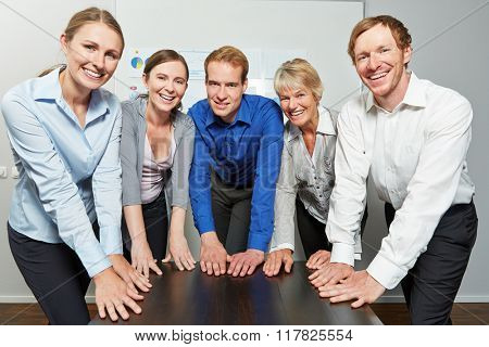 Successful business team in office putting all their hands on the table