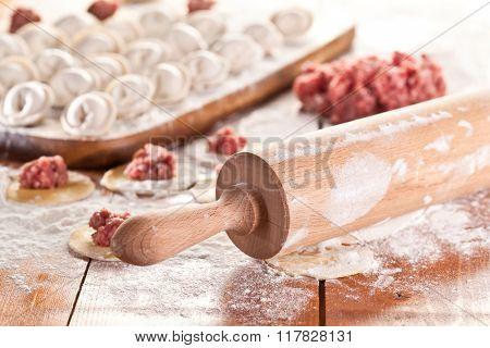 Dumplings. Uncooked on the wooden desk.