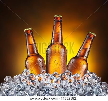 Three bottles of beer in the ice cubes on the yellow background.