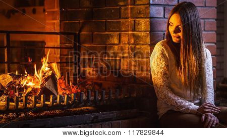 Pensive Woman Relaxing At Fireplace. Winter Home.