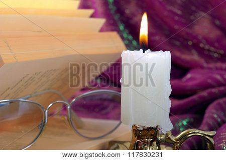 Still-life with a candle and a book