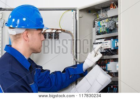 Male Electrician Testing Fusebox
