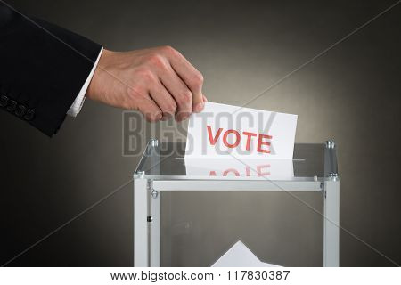 Businessperson Hand Putting Vote Into A Ballot Box