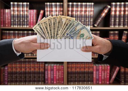 Man Hands Passing Bribe In Envelope