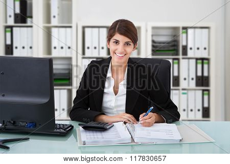 Female Accountant Writing On Documents
