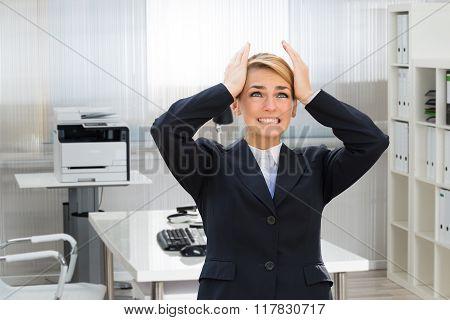 Businesswoman Suffering From Headache In Office