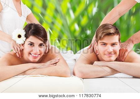 Happy Young Couple Receiving Shoulder Massage At Spa