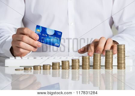 Businessman Shopping Online With Stacked Coins At Desk