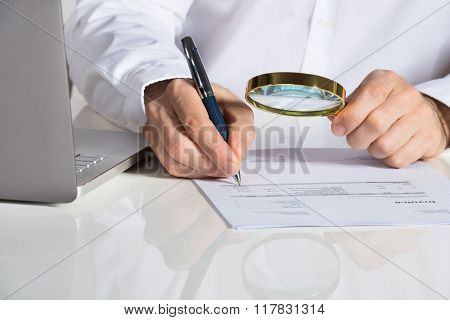 Businessman Analyzing Invoice With Magnifying Glass