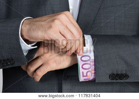 Businessman Putting Bribe In Suit Sleeve