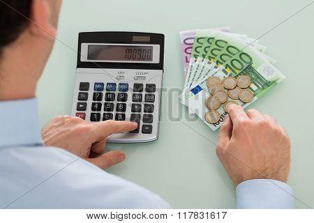 Businessperson Using Calculator On Desk