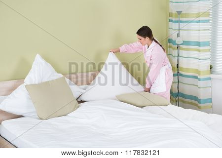 Female Housekeeper Arranging White Pillows On Bed