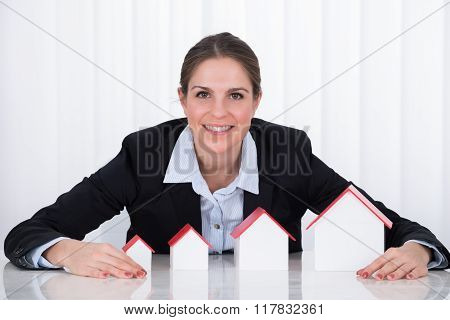 Businesswoman With Different Size Of House Models