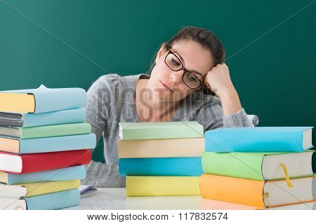 Tired Woman With Books In Classroom