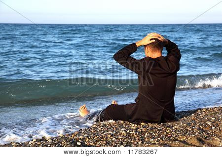 Beggarly Barefooted Man In Suit Sits Back On Stone Coast And Puts Hand On Head At Evening