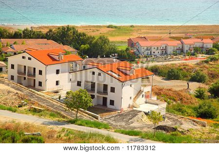 Construction Of New Two-storey White Houses With Brown Roofs On Beach
