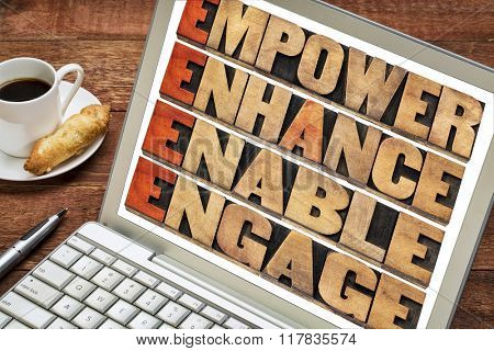 empower, enhance, enable and engage - motivational leadership and business concept - a collage of isolated words in letterpress wood type stained by red ink on a laptop with a cup of coffee