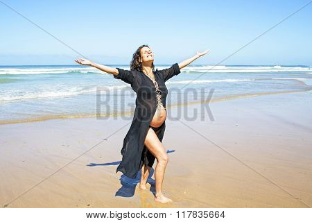 Happy pregnant woman on the beach at the atlantic ocean