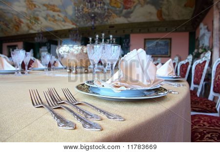 Four Forks And Two Plates With Placemat At The Brink Of Dinner Table In Restaurant