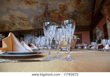 Three Cut-glass Gobles Stand On Big Dinner Table Near Knives And Plates With Placemats