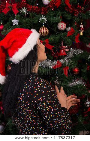 Back Of Woman Wishing At Christmas Tree