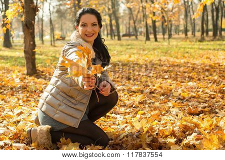 Happy Woman Giving Autumn Leaves
