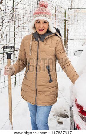 Smiling Woman Holding Snow Shovel