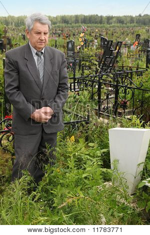 Old Sad Senior In Grey Suit Standing Near Grave With White Gravestone At Cemetery
