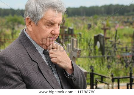 Old Sad Senior In Grey Suit Standing On Cemetery, Hand On Chin