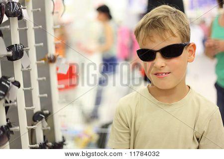 Portrait Of Little Boy versucht schwarze Sonnenbrille im Store