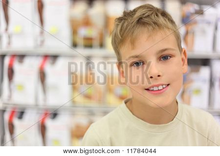 Portrait Of Little Caucasian Boy Smiling And Looking At Camera, Counter In Store With Commodity