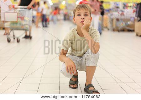 Menino sentado sozinho no Hunkers na grande loja, queixo por lado, olhando para cima