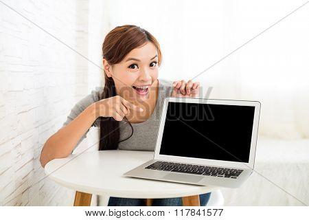 Asian woman showing laptop screen