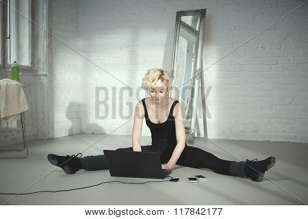 Female dancer sitting on floor using laptop computer.