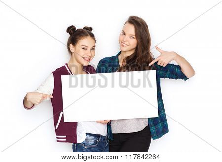 people, friends, teens and friendship concept - happy smiling pretty teenage girls holding and pointing finger to white blank board