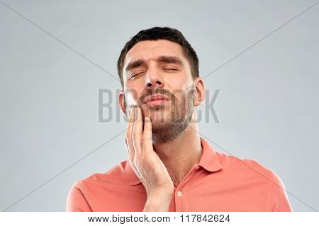 people, healthcare, dentistry and problem concept - unhappy man suffering from toothache over gray background