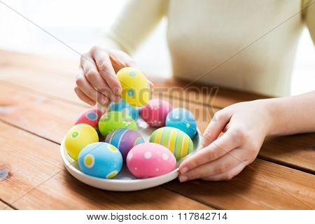 easter, holidays, tradition and people concept - close up of woman hands with colored easter eggs on plate