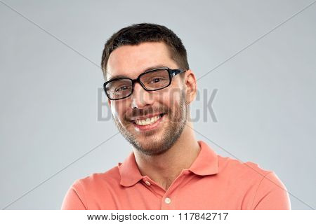 business, people and eyesight concept - portrait of happy smiling man in eyeglasses over gray background