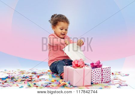 childhood, birthday, party, holidays and people concept - happy smiling little african american baby girl with gift boxes playing with shopping bag and sitting on floor over pink violet background