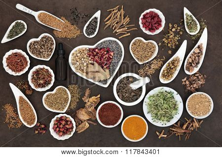 Herb selection used in female alternative herbal medicine with dropper bottle and mortar with pestle over lokta paper background.