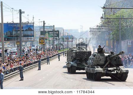 As pessoas olha para armamento e tanque na estrada em desfile