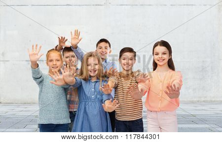 childhood, friendship, gesture and people concept - happy smiling children waving hands over urban street background