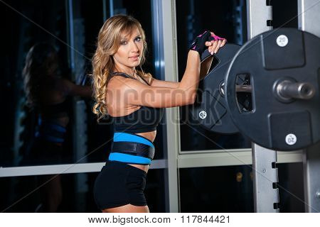 sexy young girl in belt bodybuilder resting after squat exercises. Fitness blonde woman