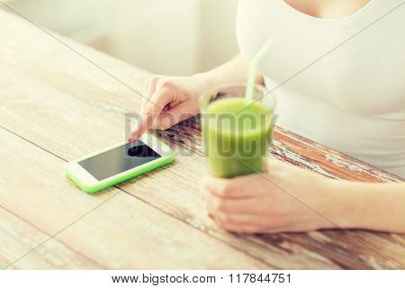 healthy eating, diet, detox, technology and people concept - close up of woman with smartphone and green juice sitting at wooden table