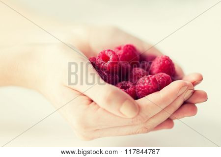 healthy eating, dieting, vegetarian food and people concept - close up of woman hands holding raspberries at home