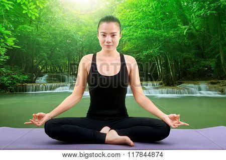 beautiful asian woman yoga meditation in front of natural deep forest tropical water falls