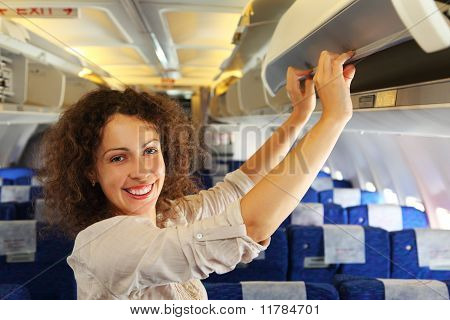 Young Beautiful Woman On Airplane Adds Baggage