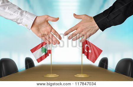 Lebanon and Turkey diplomats shaking hands to agree deal